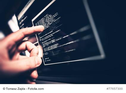 Hand zeigt auf Computermonitor mit Codefragment